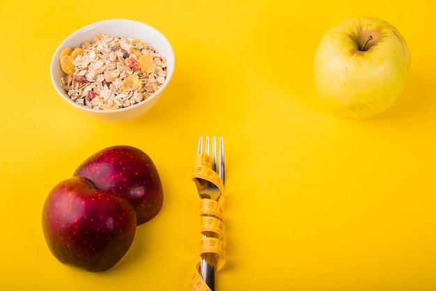 Tenedor en cinta métrica entre frutas y tazón de muesli.