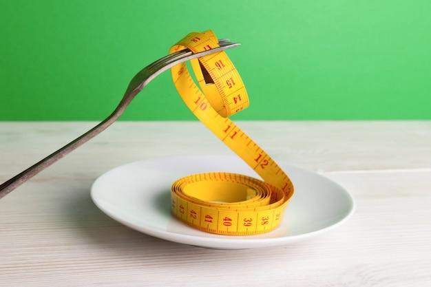 Tenedor y cinta métrica en el platillo.