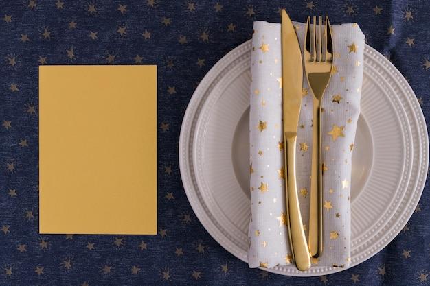 Tenedor y cuchillo de oro en plato con papel