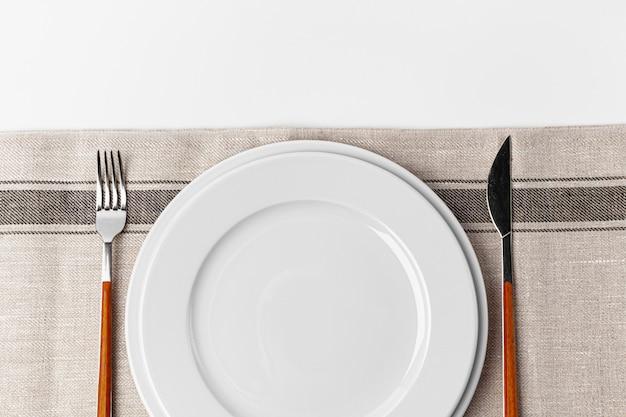 Tenedor, cuchillo y plato sobre toalla