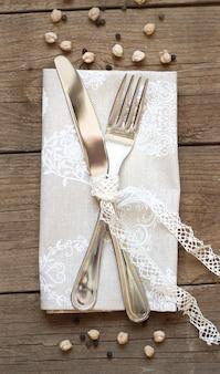 Tenedor y cuchillo en una servilleta en una vieja mesa de madera vista superior