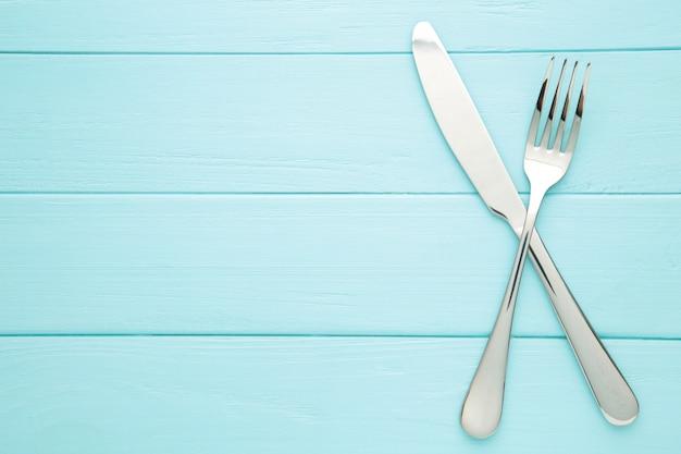 Tenedor y cuchillo sobre una mesa de madera azul