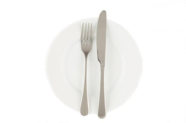 Tenedor y cuchillo sobre una placa blanca.