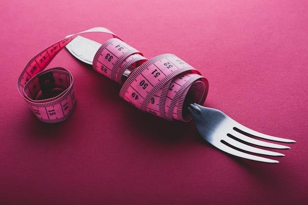 Tenedor envuelto en cinta métrica sobre fondo rosa