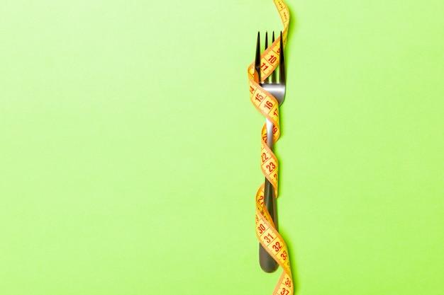 Tenedor envuelto en cinta métrica en verde, vista superior del concepto de comer en exceso