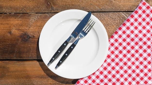 Tenedor y navaja en un plato blanco y servilleta sobre la mesa de madera
