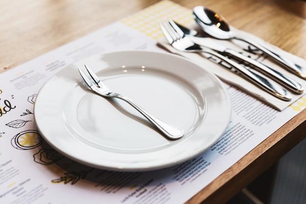 Tenedor de ostra con cubiertos: cuchara, tenedor y cuchillo en un plato de cerámica blanca. artículos de comida bañados en plata.