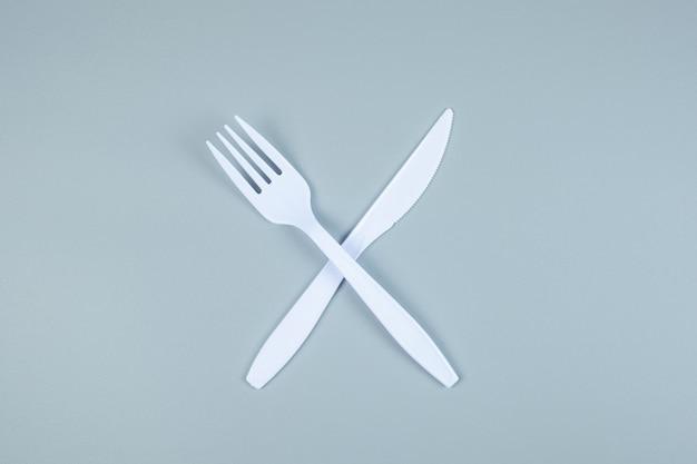 Tenedor de plástico blanco y cuchillo en gris con espacio de copia de texto. protección del medio ambiente, cero residuos, reutilizable, decir no plástico, concepto del día mundial del medio ambiente y del día de la tierra