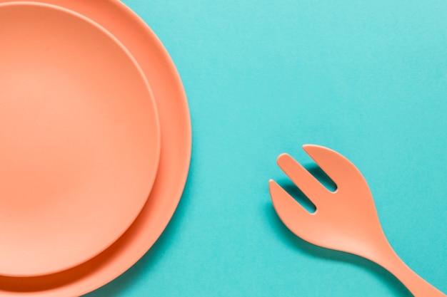 Tenedor y platos sobre fondo azul