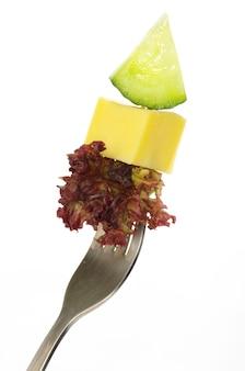 Tenedor con rúcula, queso y fruta.