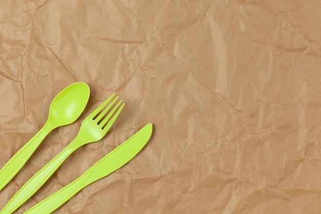 Tenedor verde reciclable reutilizable, cuchara, cuchillo hecho de almidón de maíz sobre papel artesanal arrugado marrón, copia espacio.