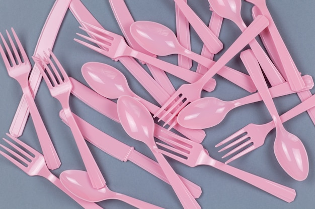 Tenedores, cucharas y cuchillos rosa reciclables reutilizables hechos de almidón de maíz sobre papel gris. eco, cero residuos, alternativa al concepto de plástico. vista plana, vista superior. horizontal. de cerca