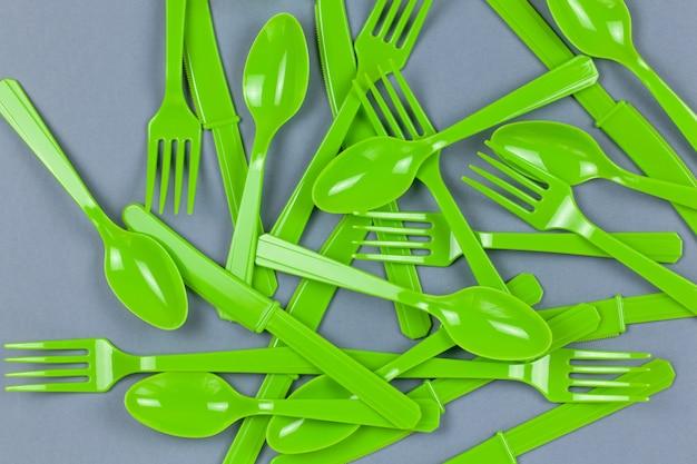 Tenedores, cucharas y cuchillos verdes reciclables reutilizables hechos de almidón de maíz sobre papel gris. eco, cero residuos, alternativa al concepto de plástico. vista plana, vista superior. horizontal. de cerca