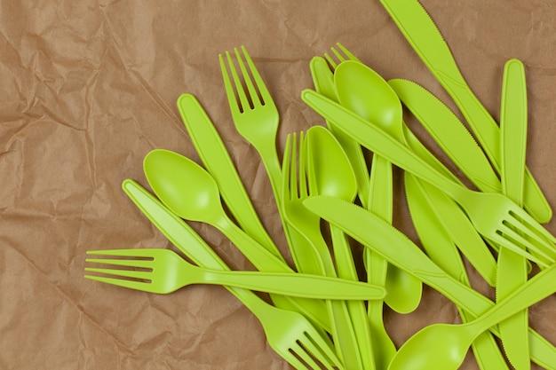 Tenedores, cucharas y cuchillos verdes reciclables reutilizables hechos de almidón de maíz sobre papel marrón arrugado.