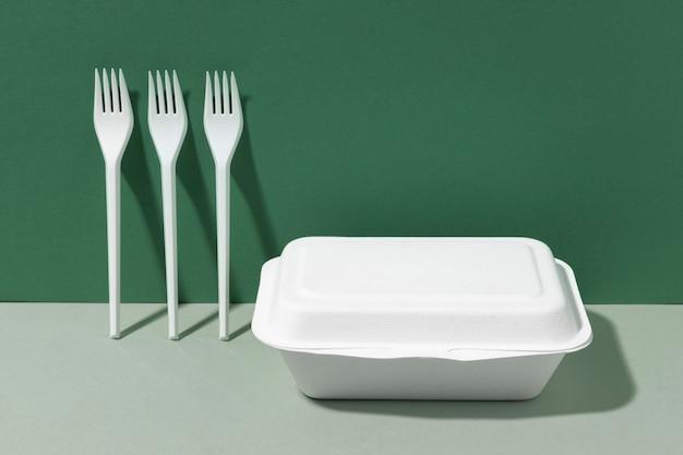 Tenedores de plástico blanco y recipiente de comida rápida.