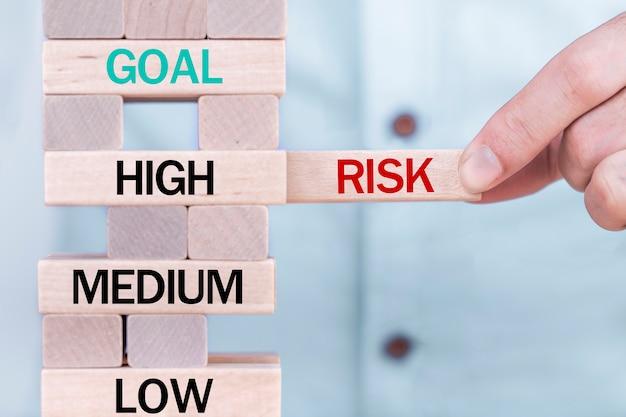 La tenencia de la mano elige los cubos del bloque de madera con palabra del riesgo. concepto de gestión de riesgos.