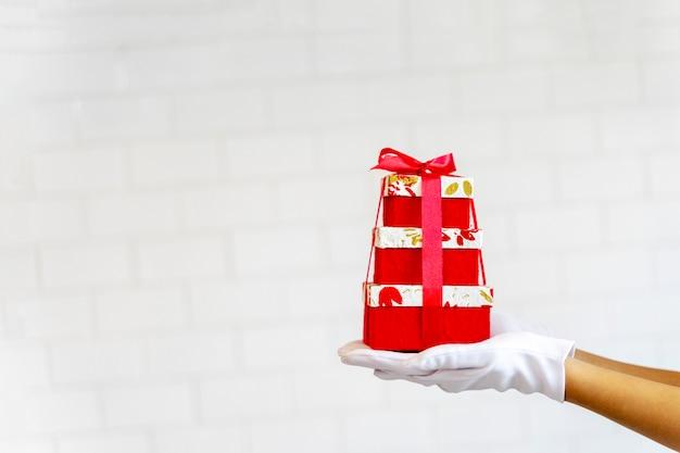 Tenencia de la mano del primer apilada de las cajas de regalo rojas en el fondo blanco.