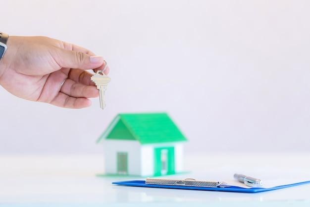 Tenencia masculina del hombre de negocios, dando las llaves de la casa, primer de la mano, interior