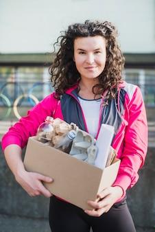 La tenencia sonriente de la mujer recicla la caja de cartón