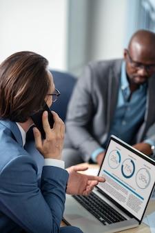 Tener algunas preguntas. hombre de negocios ocupado llamando a un socio mientras tiene algunas preguntas sobre el proyecto