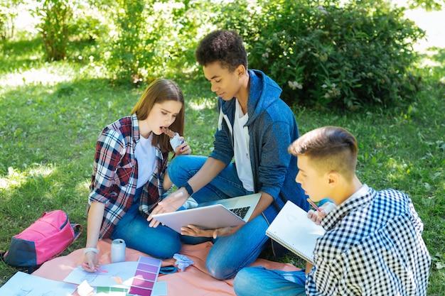 Tener descanso. estudiantes rubios comiendo barra de chocolate después de un descanso con sus mejores amigos en la naturaleza