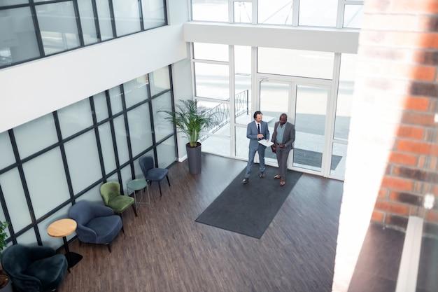 Tener la reunión. hombres de negocios caminando en el centro de negocios mientras tienen la reunión por la mañana