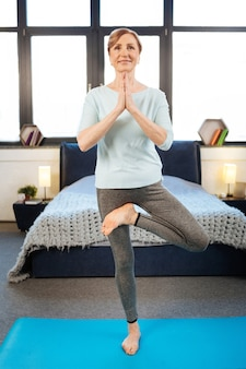 Tener una sesión de yoga. sonriente dama de cabello claro vistiendo un traje cómodo durante el entrenamiento de yoga mientras está de pie en el dormitorio sobre la alfombra
