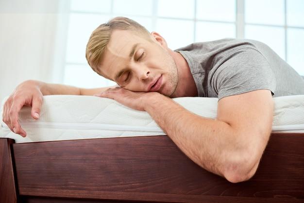 Tener una siesta joven apuesto durmiendo en un colchón blanco ortopédico grande y cómodo