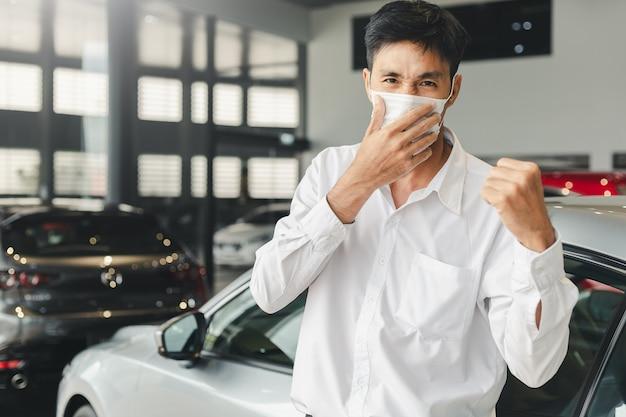 Tenga cuidado antes de conducir este hombre que trabaja virus infectado covid-19 o corona mostrar síntomas mientras conduce debe protegerse en la sala de exposición concesionario estación automotriz automotriz