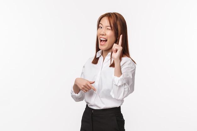 Tengo una idea. la mujer asiática creativa e inteligente con camisa blanca tiene un plan, guiña un ojo para asegurar que todo esté bien, levanta el dedo índice en un gesto de eureka y sonríe complacida, una solución pensante