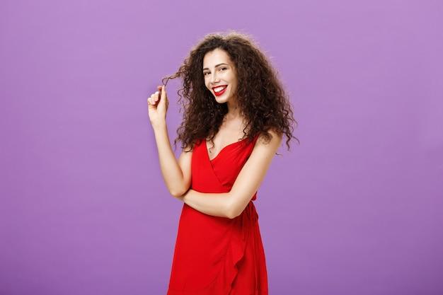 Tengo mis ojos puestos en ti sensual y coqueta atractiva mujer caliente de pelo rizado en vestido de noche rojo jugando ...
