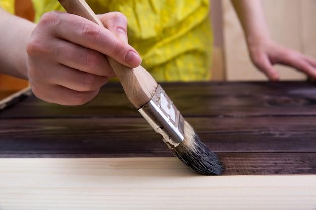 Teñido en el color oscuro de la madera clara con un pincel.