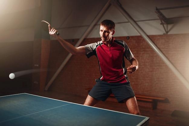 Tenis de mesa, jugador masculino con raqueta en acción, pelota con rastro. entrenamiento de ping pong indoor