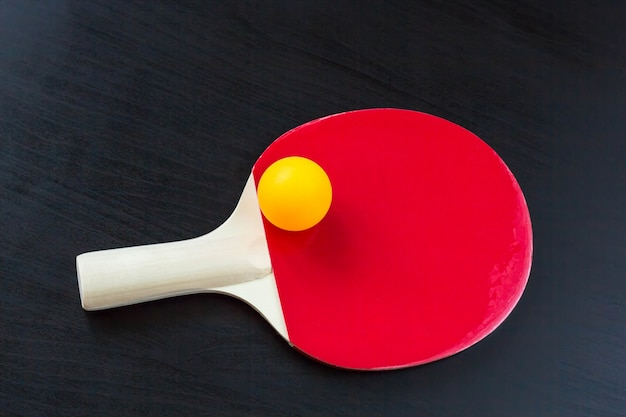 Tenis de mesa o raqueta de ping pong y pelota sobre un fondo negro