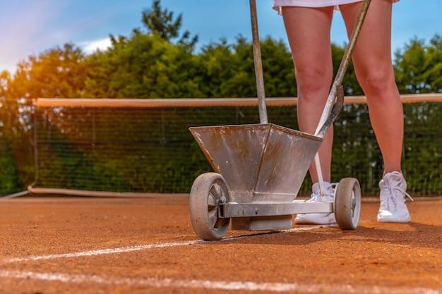 Tenista marca una línea blanca lima en una cancha de tenis