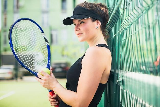 Tenista muy femenina sosteniendo una raqueta al aire libre