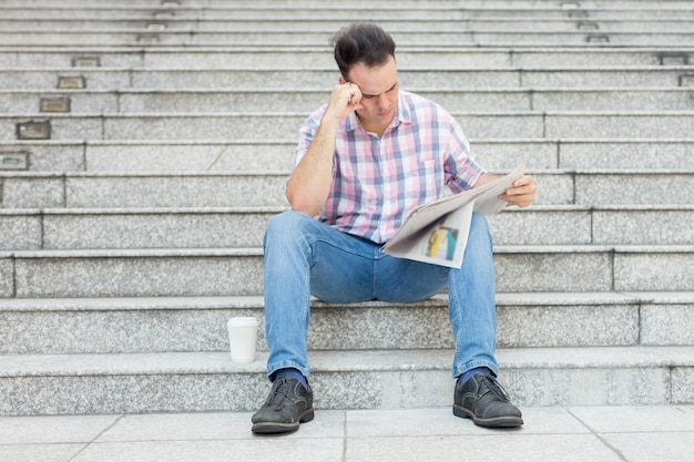 Tensed man reading newspaper on city stairway