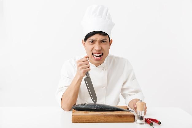 Tenso jefe japonés en uniforme de cocinero blanco cocinando y fileteado de pescado fresco crudo con un cuchillo aislado sobre una pared blanca