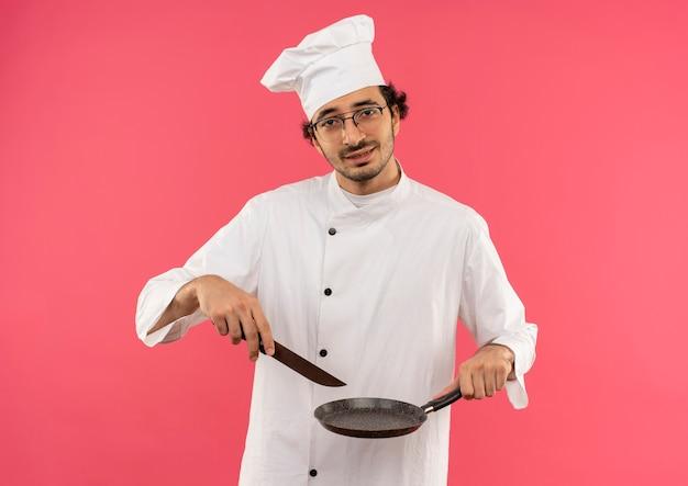 Tenso joven cocinero vistiendo uniforme de chef y gafas sosteniendo una sartén y un cuchillo