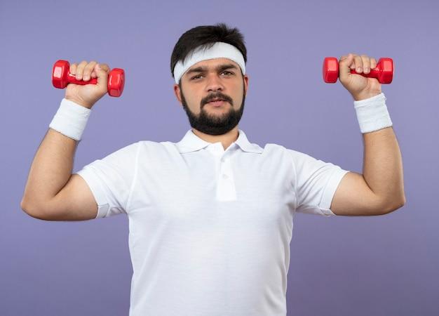 Tenso joven deportivo vistiendo diadema y muñequera haciendo ejercicio con pesas