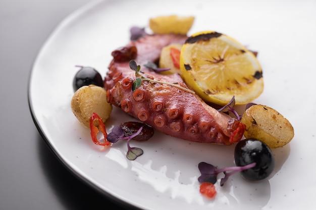Tentáculos de pulpo con limón en un plato blanco