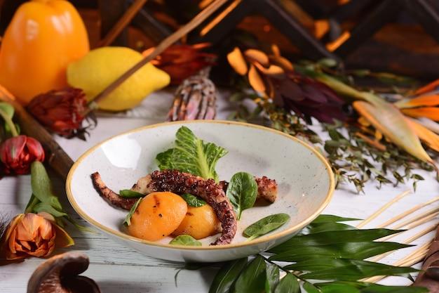 Tentáculos de pulpo a la plancha con durazno. sobre una mesa de madera blanca con una decoración de flores.