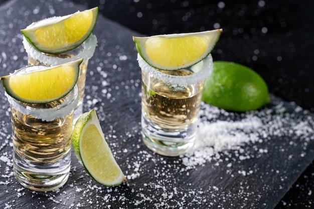 Tequila con lima y sal sobre negro