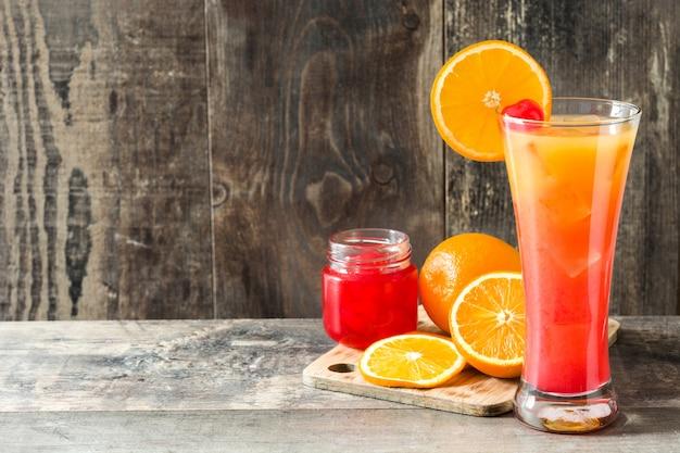 Tequila sunrise cóctel en vidrio en la mesa de madera.