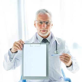 Terapeuta amistoso que muestra el sujetapapeles vacío