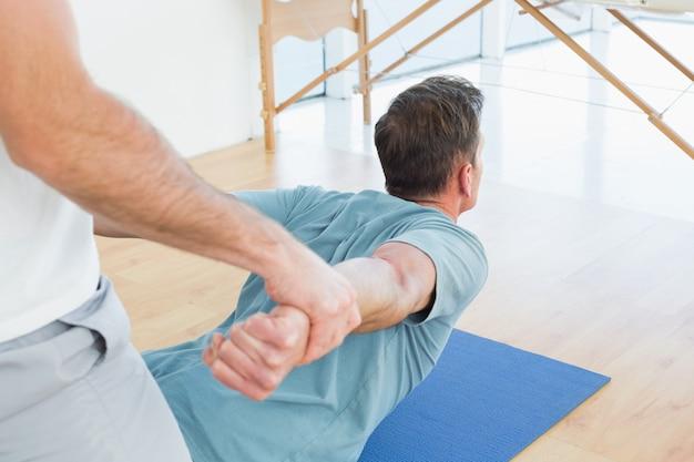 Terapeuta ayuda al hombre con ejercicios de estiramiento