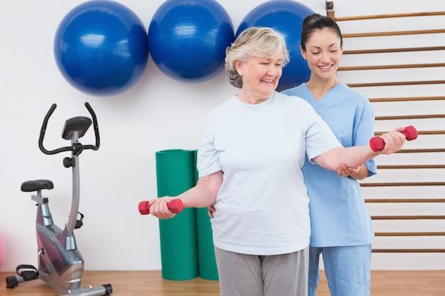 Terapeuta ayuda a mujer mayor ajuste pesas