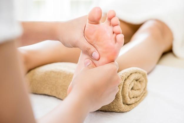 Terapeuta dando masaje relajante de pies de reflexología tailandesa a una mujer en spa