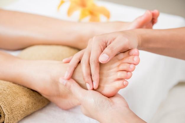 Terapeuta dando relajante masaje de reflexología tradicional de pies a una mujer en spa