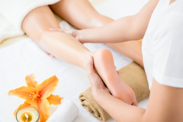 Terapeuta dando relajante tratamiento de masaje de piernas de aceite tailandés a una mujer en spa